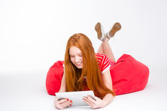 Sensual smiling young lady lying on red beanbag using tablet Royalty Free Stock Image
