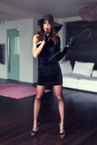Sensual strict dominatrix lady in hat and whip posing. Indoor royalty free stock images
