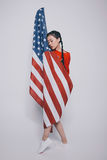 Sensual stylish asian girl with closed eyes wrapped in american flag and stanging isolated on grey Stock Photography