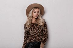 Sensual stylish young woman in a vintage stylish leopard sweater in fashionable black leather pants in a luxurious beige hat. Posing indoors near a white wall royalty free stock images