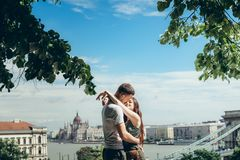 Sensual sunny portrait of the beautiful couple in love tenderly hugging at the background of the charming view of. Budapest, Hungary Royalty Free Stock Images