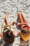 Sensual tanned blonde and brunette having beers Stock Photos