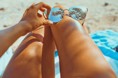 Sensual tanned female legs with fashionable sunglasses. Close-up outdoor photo of sensual tanned female legs with fashionable sunglasses Stock Images