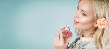 Sensual tender delicate young woman enjoying her perfume on blue Stock Image
