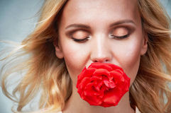 Sensual tender young woman portrait with breeze hair and rose in. Sensual tender delicate young woman portrait with breeze hair and rose in mouth, enjoyment royalty free stock photo