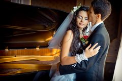 Sensual wedding portrait. The handsome groom is tenderly kissing his beautiful bride in the forehead at the background. Of the piano Stock Photo
