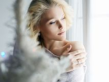 Home lifestyle girl looking in window. Sensual winter beautiful young blond woman. home lifestyle girl looking in window stock photo