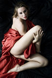 Sensual woman. Blonde girl with red silk that seeks the pleasure Stock Photography