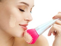Sensual woman applying dry cosmetic tonal foundation on the face using makeup pink brush. Stock Photos