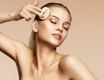 Sensual woman applying dry powder using cosmetic cushion on her facial skin. Photo of attractive girl with perfect makeup on beige background. Beauty concept royalty free stock images
