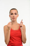 Sensual woman applying gloss on her lips. Make-up artist paints lips with gloss. Professional make-up Stock Images