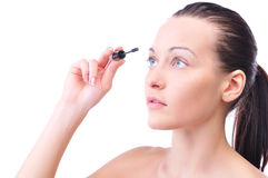 Sensual woman is applying mascara Stock Images