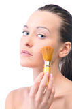 Sensual woman is applying powder. Young attractive sensual woman is applying cosmetics on her face and looking at camera, isolated on white Stock Photos