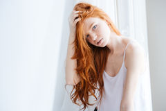 Sensual woman with beautiful red hair standing near window Stock Photography