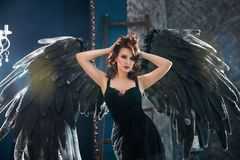 Sensual woman in black angel costume. Attractive sensual woman posing in black angel costume with big wings Stock Photos