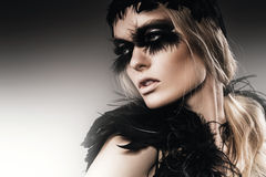 Sensual woman with black feathers on eyes Stock Images