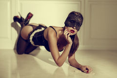 Sensual woman in black underwear and eye cover kneeling vintage Stock Photography