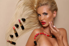 Sensual woman with blond hair with posing with a lot of lipsticks. Fashion studio portrait of beautiful sensual woman with blond hair with posing with a lot of Royalty Free Stock Image