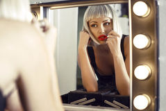 Sensual woman in blond wig doing makeup in dressing room Stock Photos