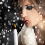 Sensual woman blowing candle in snow Royalty Free Stock Photo