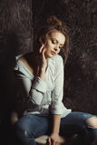 Sensual woman in blue ripped jeans and shirt in the shadows Royalty Free Stock Image