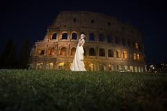 Sensual woman body. Pretty bride near Coliseum. Sensual woman body. Beautiful bride in long white dress standing on green grass near famous Italian sightseeing Stock Photography
