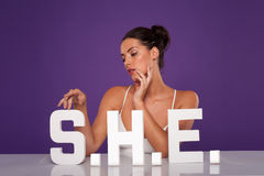 Sensual woman caressing the letters S.H.E Royalty Free Stock Photography