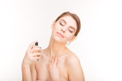 Sensual woman with closed eyes applying parfume on her neck. Beauty portrait of sensual young woman with closed eyes applying parfume on her neck over white royalty free stock images