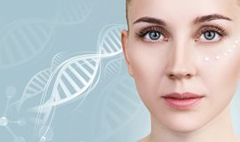 Sensual woman with cream dots on face in DNA chains. Over blue background stock image