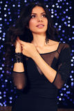 Sensual woman with dark curly hair in elegant black dress with accessories Stock Photography