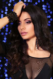 Sensual woman with dark curly hair in elegant black dress with accessories Royalty Free Stock Photography