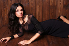 Sensual woman with dark curly hair in elegant black dress with accessories Stock Images