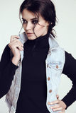 Sensual woman with dark  hair and bright makeup, in jeans jacket Stock Photo
