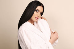 Sensual woman with dark hair and bright makeup,wearing white cozy bathrobe Stock Images