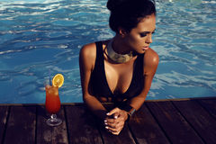 Sensual woman with dark hair in elegant black swimsuit Stock Photos