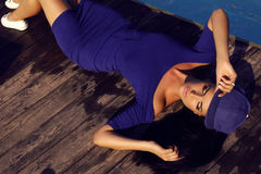 Sensual woman with dark hair relaxing beside swimming pool Royalty Free Stock Photography