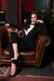 Sensual woman with dark hair wearing elegant black suit royalty free stock images