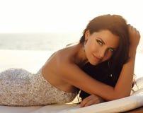 Sensual woman with dark hair wears luxurious dress Stock Photo