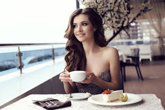 Sensual woman drinking coffee in outdoor summer cafe Royalty Free Stock Image