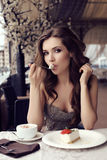 Sensual woman eating dessert in outdoor summer cafe. Fashion outdoor photo of beautiful sensual woman with long dark hair in luxurious sequin dress posing in Royalty Free Stock Photography