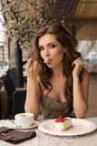 Sensual woman eating dessert in outdoor summer cafe. Fashion outdoor photo of beautiful sensual woman with long dark hair in luxurious sequin dress posing in Stock Photo