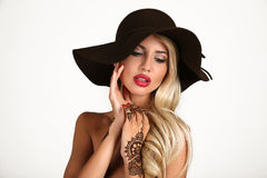 Sensual woman in elegant black hat with henna tattoo on hands Royalty Free Stock Photos