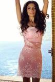 Sensual woman in elegant dress relaxing beside swimming pool Royalty Free Stock Image