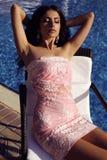 Sensual woman in elegant dress relaxing beside swimming pool Royalty Free Stock Images