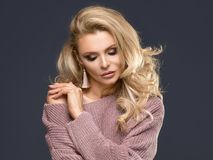 Sensual woman in fashionable sweater. Sensual female model posing in fashionable sweater. Blonde beautiful woman with glamour makeup and long curly hair Royalty Free Stock Photography