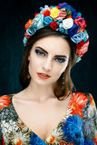 Sensual woman in floral wreath. Portrait of beautiful young woman with red lips dressed in a bright blouse Royalty Free Stock Photography