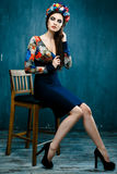 Sensual woman in floral wreath. Portrait of beautiful young woman with red lips dressed in a bright blouse Royalty Free Stock Photo
