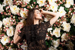 Sensual woman on flower wall background Stock Images