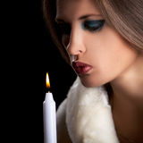 Sensual woman in fur blowing a candle on black background Royalty Free Stock Photos