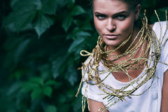 Sensual woman in golden rope on nature Royalty Free Stock Photography